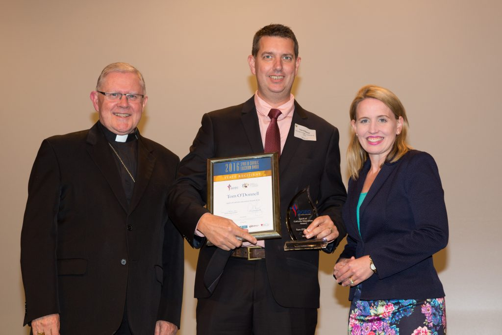 Spirit of Catholic Education Award recipient, Tom O'Donnell (centre) is presented by the Archbishop of Brisbane, Brian Coleridge and State Member for Education, the Hon Kate Jones MP.